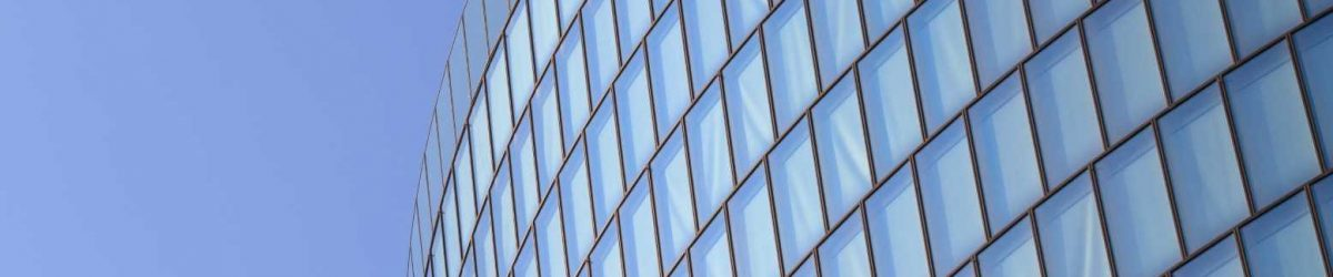 Modern,Glas,Facade,Of,Office,Tower,In,Front,Of,Blue